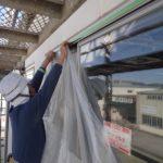 窓に吹付塗料が付かないように養生しています。