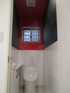2階トイレ(LIXILキャパシア):水のかかる壁部分はサッと拭き取れるキッチンパネル。上部壁は黒と赤の壁紙を使用してコンテンポラリーな雰囲気に。