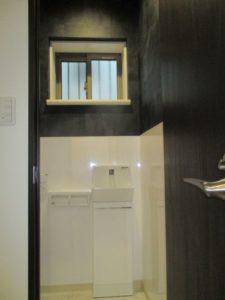 3階トイレ手洗(LIXILコフレルスリム):白のキッチンパネルと黒の壁紙でモダンな空間に