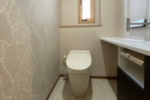 ベージュをベースとした床や壁紙で落ち着いたシックなトイレ空間に。便器LIXILサティスSタイプ・手洗いカウンターLIXILキャパシア