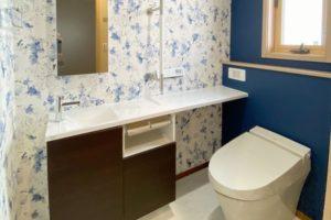 紺色と花柄のクロス、白いマーブル柄の床材の対比で美しく。便器LIXILサティスSタイプ・手洗いカウンターLIXILキャパシア