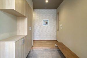 玄関~玄関ホール:ご近所の方とのおしゃべり用に腰掛カウンターを設置。正面壁にはエコカラット(グラナスルドラ ホワイト)を貼りマイセンの陶器を設置。