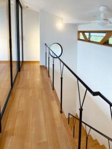 2階階段室 軽やかなオリジナルデザインの手すり シーリングファンで夏も涼しく